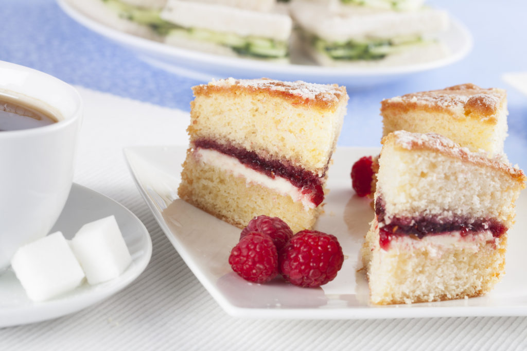 cup of tea with sugar cubes, victoria sponge with raspberries for a perfect afternoon tea